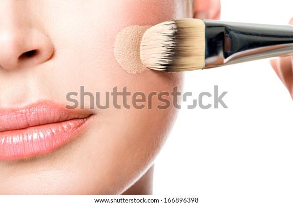 女性の顔に液体調の基礎を塗る化粧師。頬の接写