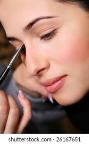 makeup artist applying mascara on the eyelashes of a beautiful girl.
