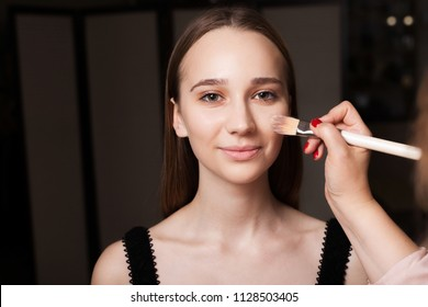 makeup artist applying the mixed foundation on a face of a young beautiful smiling model. concept of professional natural make up