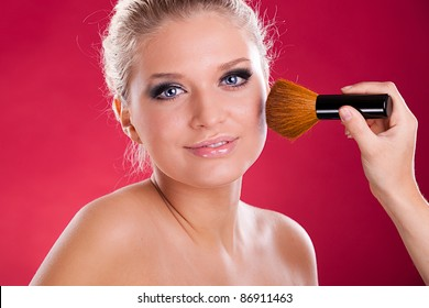 Makeup artist applying makeup on attractive young woman's face