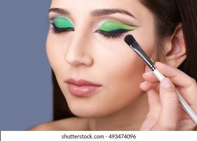 Makeup artist applying makeup on model eyes, on grey background