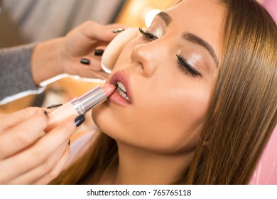 Makeup artist applying pink lipstick on young woman's lips.