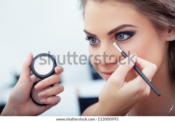 Make-up-Künstler, der in der Ecke des Motivauges eine weiße Augentschattenschatten aufträgt und eine Muschel mit einer Augentschale auf Hintergrund hält, Nahaufnahme