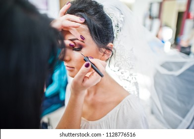 Makeup artist or beautician doing wedding makeup for a gorgeous young bride in a salon.
