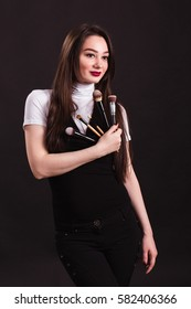 Makeup artist with brushes in hand on a black background