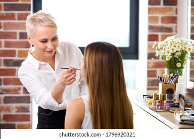make-up artist is concentrated on applying lipstick on model's face in beauty studio. visage, make-up, beauty concept