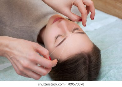 make-up artist corrects makeup, gives shape and thread plucks eyebrows in a beauty salon. Professional care for face.