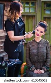 Makeup artist corrects makeup on a face of woman
