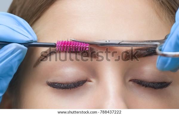 化粧師は、ハサミで眉毛を切る。美しい長いまつげとグルームの良い眉を持つ女の子。