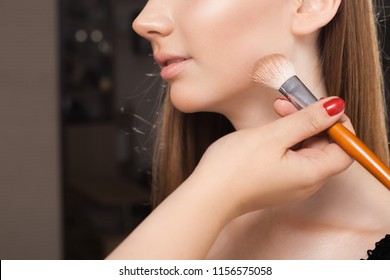 makeup artist dabbing the loose powder on a face of a young beautiful model using a brush. concept of professional make up training