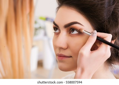 make-up artist doing make-up beautiful girl in the salon, beauty concept and style
