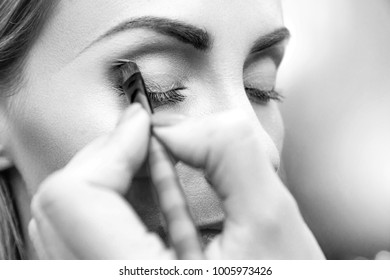 Makeup artist doing eyemakeup with brush. Eyeshadow in the corner of the eyelid. Closeup side view. Black and white photo. Unfocused background.