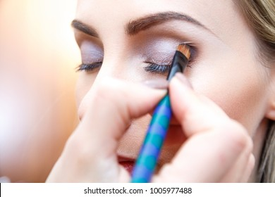 Makeup artist doing eyemakeup with brush. Nude eye shadow in the corner of the eyelid. Closeup side view. Unfocused background.