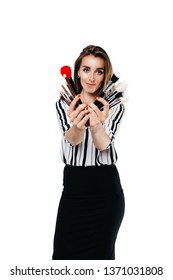 makeup artist girl on a white background holding different and different size brushes in their hands one of them is red, looks into the camera