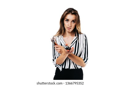 makeup artist girl in shirt and black skirt on a white background holding a small mirror with tassels in her hands