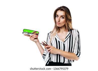 make-up artist girl in shirt and black skirt on a white background holding a small pocket mirror with a chrome and tassels in her hands