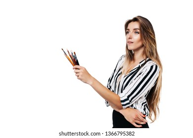 Makeup artist girl in shirt and black skirt on a white background holding a small tassels in her hands and looking to the side