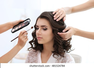 Makeup artist and hairdresser preparing bride before her wedding