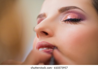 Makeup artist lines the lips of girl
