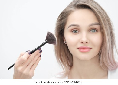 Make-up artist makes makeup beautiful blonde girl on a white background. Close-up hands with brush and face. The concept of make-up and beautiful smooth skin.
