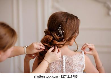 Makeup artist makes hair bride. Wedding preparations