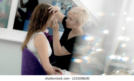 Makeup artist painting eyes of beautiful model