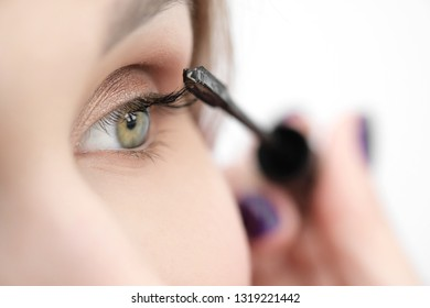 Make-up artist paints a girl with black mascara eyelashes closeup on a white background.