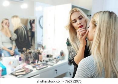 Makeup artist paints model in beauty studio