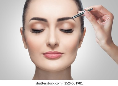 Makeup artist plucks eyebrows with tweezers to a woman before staining with henna.