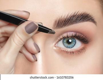 Make-up Künstler pflückt Augenbrauen mit Pinzette zu einer Frau mit lockbraunem Haar und nacktem Make-up. Schöne dicke Augenbrauen, Nahaufnahme. Professionelle Make-up und kosmetologische Hautpflege.