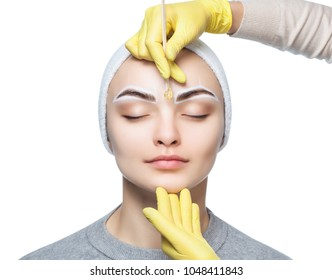 The make-up artist plucks her eyebrows, before the procedure of permanent make-up in the beauty salon.