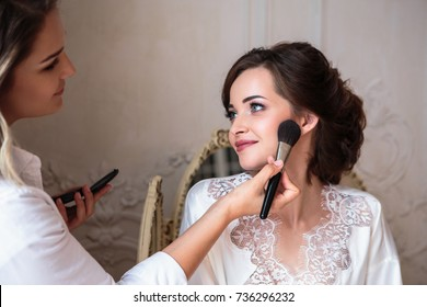 makeup artist preparing beautiful bride before the wedding in a morning