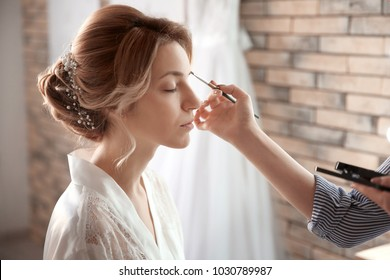 Makeup artist preparing bride before her wedding in room