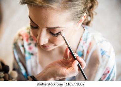 Makeup artist preparing bride before the wedding.