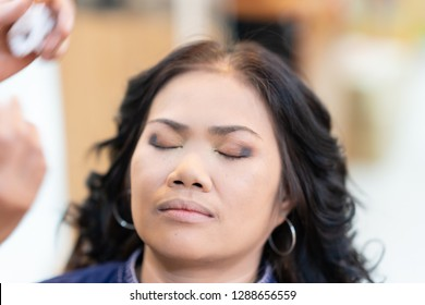 Makeup artist preparing Middle age asian woman face undergoing eyebrow correction procedure, Closeup shot eye makeup with brush on pretty woman face.