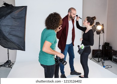 Makeup artist preparing model for photoshoot in the studio