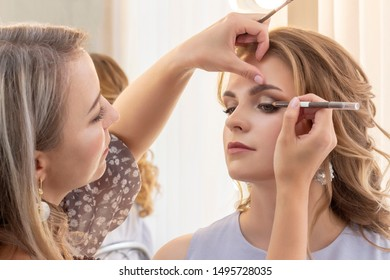 Makeup artist puts make up on girl model. wedding makeup, evening makeup, natural makeup. make-up artist puts eye shadow on eyelids.