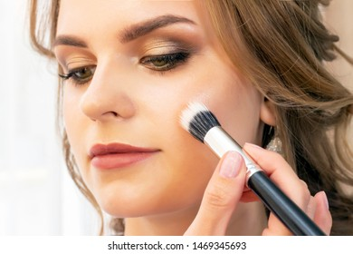 Makeup artist puts makeup on girl model. Brush powder on cheekbones and face. beautiful girl model, portrait. Nude colors in makeup. wedding, evening makeup.