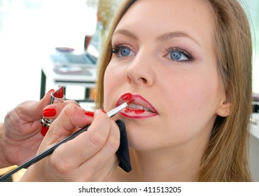 Makeup artist putting red lipstick on attractive woman lips in salon