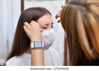 Make-up-Künstler entfernt überschüssiges Augenbrauenhaar mit einem Faden in einem Schönheitssalon während der Covid-19-Pandemie.
