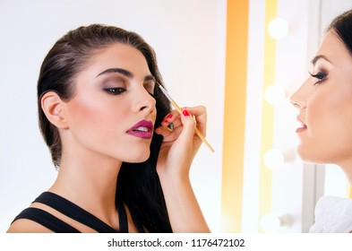 Makeup artist shaping  eyebrows to attractive young woman
