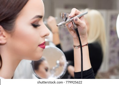 Makeup artist using airbrusher.
