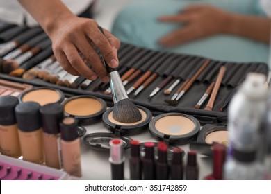 Make-up artist using natural animal hair brush to apply pressed powder