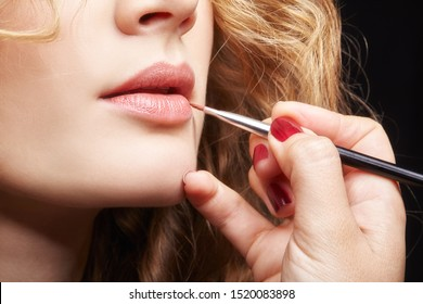 Makeup artist visagiste using brush for application lipstick on lips of young caucasian model with wavy ginger hair. Beauty and fashion concept.
