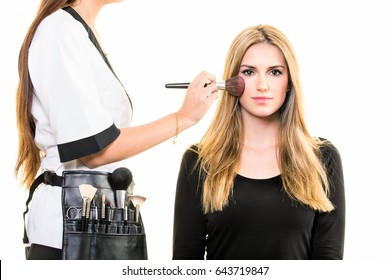 Makeup artist wearing a belt of tools and brushes applying blusher to the cheek of a young woman with long blond hair using a large soft bristle cosmetics brush in a beauty salon isolated on white