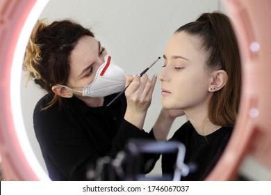 Makeup artist wearing a medical mask.