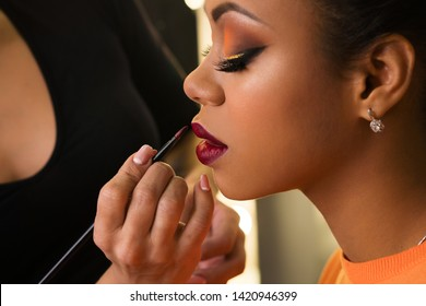 Makeup artist working with African American model in beauty salon. Perfect skin facial. Beautiful fashion luxury makeup orange-coloured shades. Big lush beautiful lips. Sexy violet purple pucker.