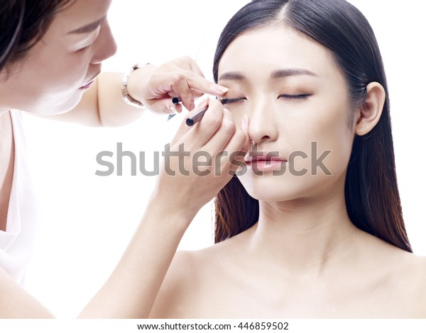 makeup artist working on a beautiful young female asian model, isolated on white background.