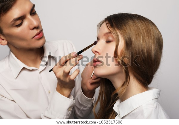 make-up artist, young male, doing make-up beautiful girl, beauty concept