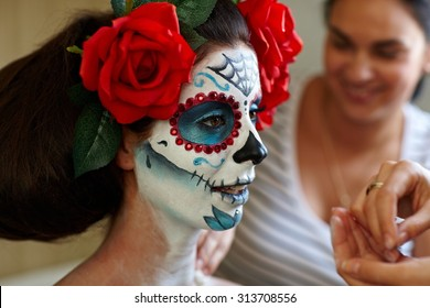 Makeup artists in work making a Halloween makeup - mexican Santa Muerte mask.